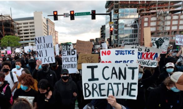 Protesters hold up signs during a demonstration over the death of George Floyd in Boston, Massachusetts, 31 May