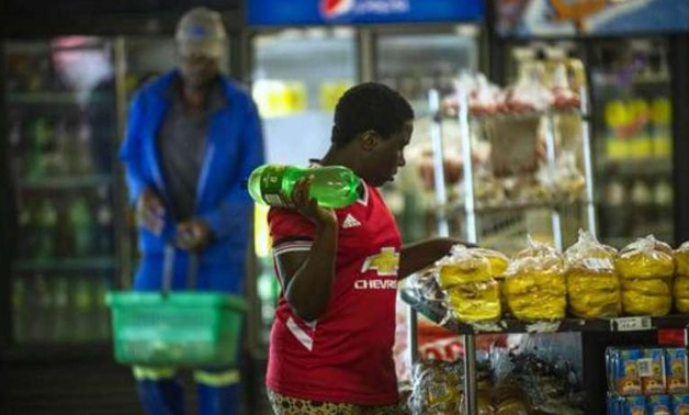 A woman holding a bottle of soft drink as she shops around at a local supermarket in the Township of Zandspruit, Greater Johannesburg, South Africa - AFP