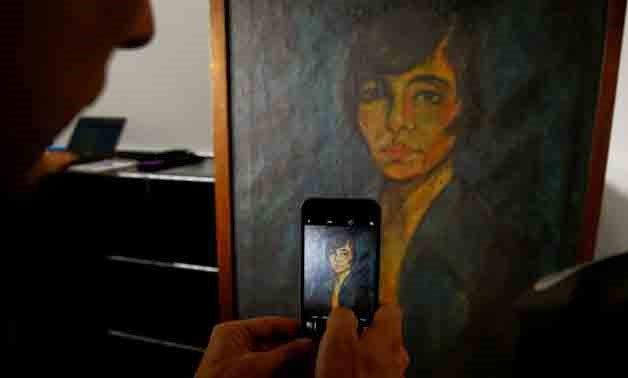 A man uses his mobile phone as he takes a picture of the painting 'Maschka' by late German artist Otto Mueller during a news conference, REUTERS