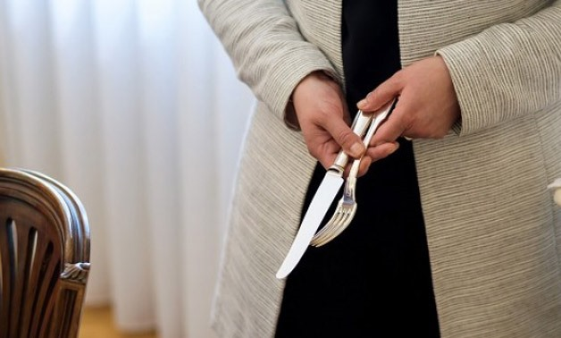 A teacher holds a knife and a fork during a lesson at Switzerland's finishing school Institut Villa Pierrefeu on June 26, 2017 in Glion. PHOTO: AFP
