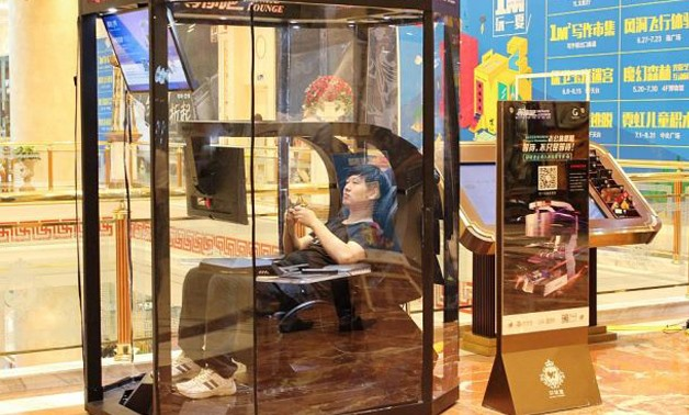 A man playing video games in a booth at a shopping mall in Shanghai. China has the solution for weary men in shopping malls everywhere: so-called husband rest booths. - AFP