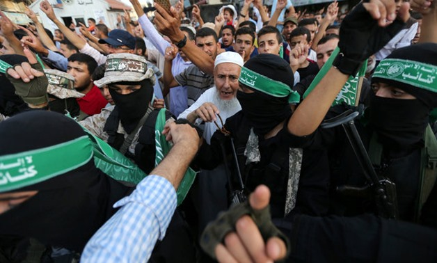 Palestinians and Hamas militants chant slogans during a military show against Israel's newly-installed security measures at the entrance to the al-Aqsa mosque compound in Khan Younis in the southern Gaza Strip