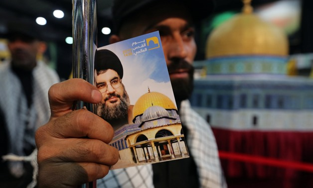 A Hezbollah member holds a placard depicting Lebanon's Hezbollah leader Sayyed Hassan Nasrallah and Dome of the Rock during a rally marking Al-Quds day in Beirut's southern suburbs, Lebanon June 23, 2017. REUTERS/Aziz Taher