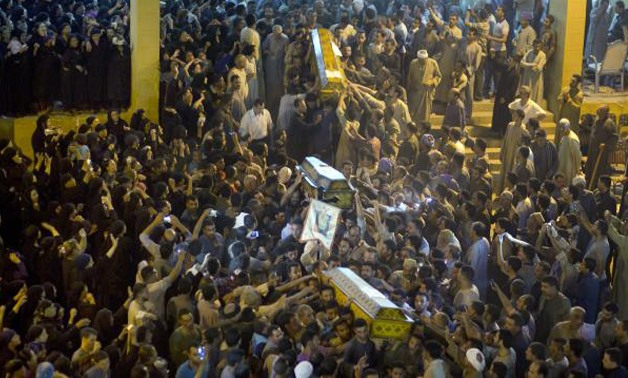 Relatives of Coptic Christians carry coffins of their relatives who were killed during a bus attack, following their funeral service, at Abu Garnous Cathedral in Minya, Egypt. Picture: AP