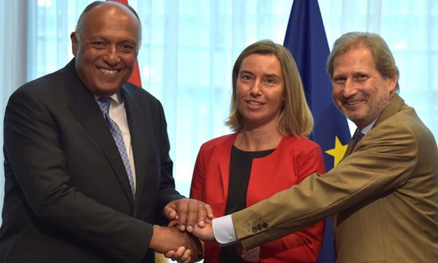 European Union foreign policy chief Federica Mogherini, European Neighborhood Policy and Enlargement Negotiations Commissioner Johannes Hahn and Egypt's Minister for Foreign Affairs Sameh Hassan Shoukry shake hands as they attend a EU-Egypt Association Co