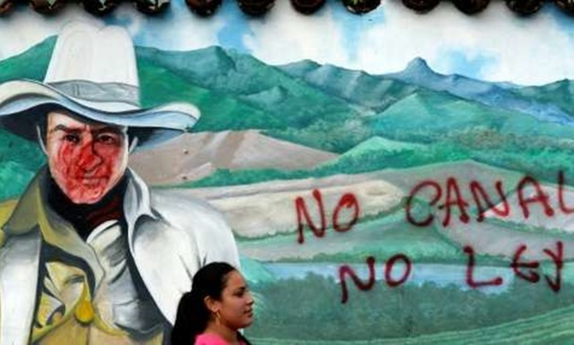 "A woman is seen in front of a wall with a graffiti reading ""No canal, no law"" during a protest against the construction of an inter-oceanic canal in Juigalpa, Nicaragua on June 13, 2015"