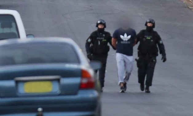PHOTO: NSW Police lead suspects away after raids in Sydney.