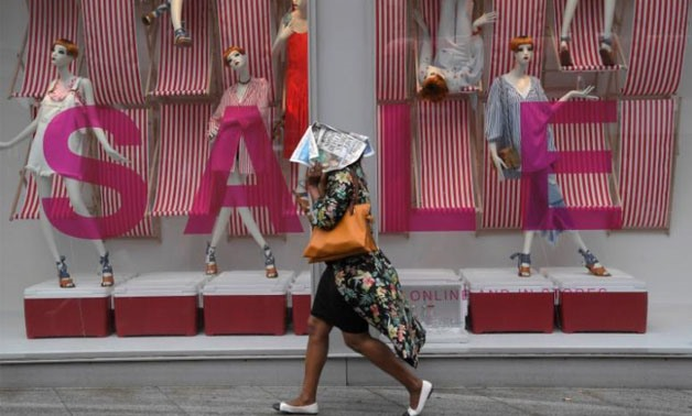 A shopper shields herself from the rain with a newspaper as she walks past a store on Oxford Street in London, Britain June 27, 2017- Reuters