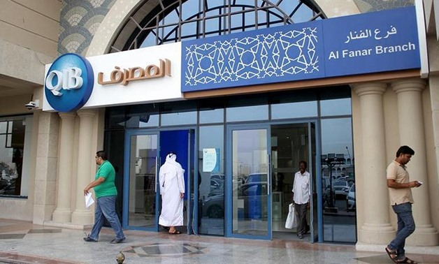 Customers leave one of the branches of Qatar Islamic Bank in Doha April 13, 2016