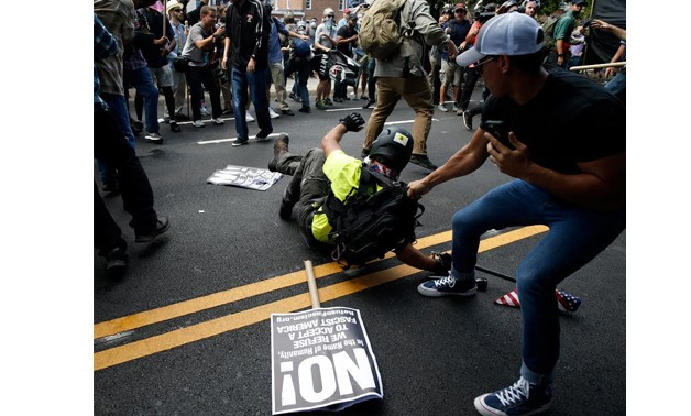 A man is pulled on after falling on the pavement during a clash between members of white nationalist protesters against a group of counter-protesters in Charlottesville, Virginia, U.S., August 12, 2017. REUTERS/Joshua Roberts