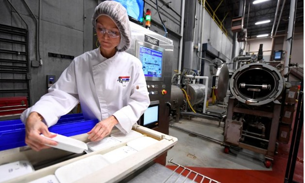 Lea M Mohr, Director of Technical Services, prepares packages for the MATS-B machine as she makes packaged meals at an Ameriqual facility with new microwave technology that Amazon.com Inc is evaluating, in Evansville, Indiana, U.S. August 9, 2017.