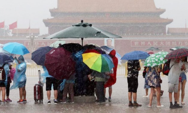 Tourists hold umbrellas as they visit Tiananmen Square during a rainstorm in Beijing, China August 12, 2017 – REUTERS/Stinger