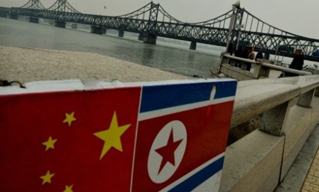 © AFP/File | The Chinese and North Korean flags attached to a railing as trucks carrying Chinese-made goods cross into North Korea on the Sino-Korean Friendship Bridge at the Chinese border town of Dandong on December 18, 2013