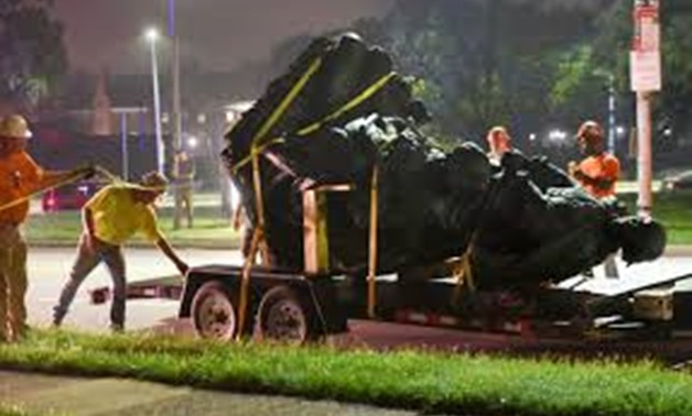 Workers remove a monument dedicated to the Confederate Women of Maryland early Wednesday after it was taken down in Baltimore. | Jerry Jackson/The Baltimore Sun, distributed by the Associated Press -REUTERS