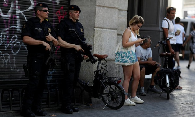 Armed Catalan Mossos d'Esquadra officers stand guard a day after a van crashed into pedestrians at Las Ramblas in Barcelona - REUTERS