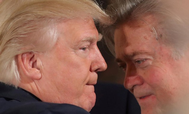 U.S. President Donald Trump talks to chief strategist Steve Bannon during a swearing in ceremony for senior staff at the White House in Washington, U.S. January 22, 2017.