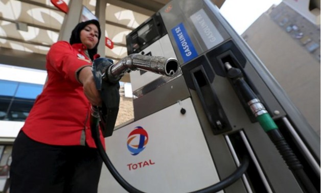 A female employee poses with a fuel pump at a petrol station in Cairo -Mohamed Abd El Ghany- Reuters