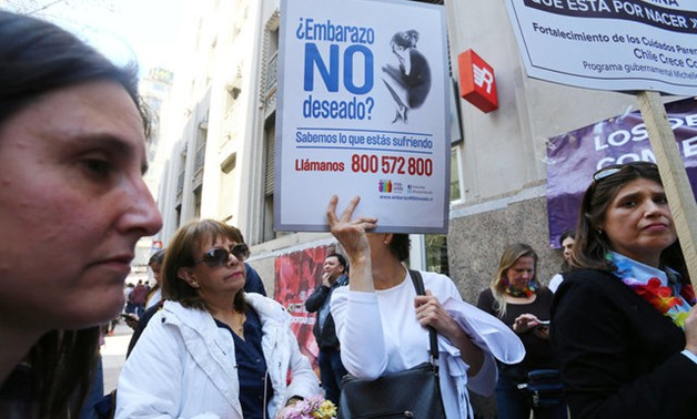 A demonstrator against abortion hold a placard during a rally in Santiago - REUTERS