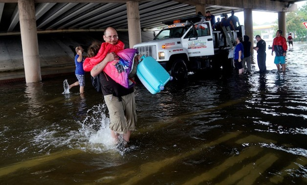 A man carries a child after being evacuated by dump truck from the Hurricane Harvey floodwaters in Dickinson, Texas August 28, 2017. — Reuters pic