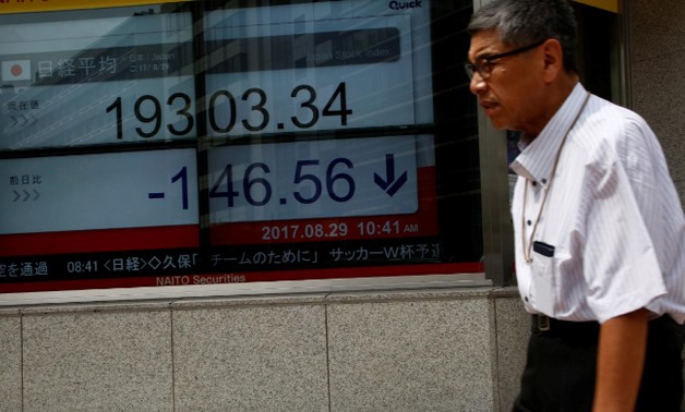 A man walks past an electronic board showing Japan's Nikkei average outside a brokerage at a business district.