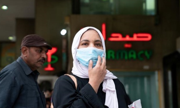 FILE PHOTO: A woman wears a protective face mask, following the outbreak of the new coronavirus, in Kuwait, February 25, 2020. REUTERS/Stephanie McGehee/File Photo