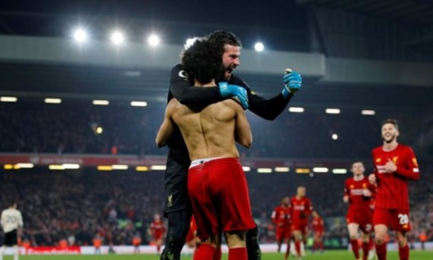 Liverpool's Mohamed Salah celebrates scoring with Alisson. -Reuters