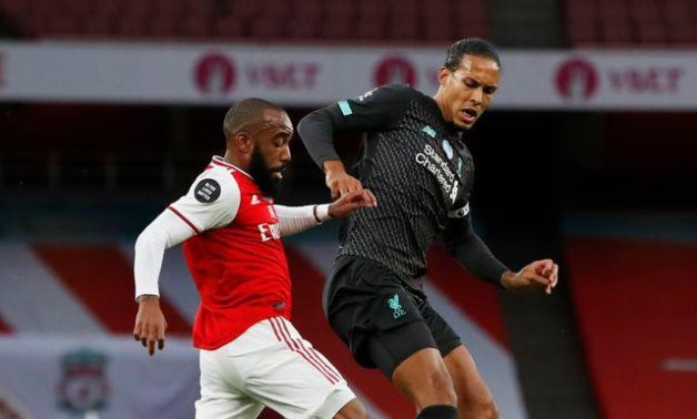 Lacazette in action with Liverpool's Virgil van Dijk, as play resumes behind closed doors following the outbreak of the coronavirus disease (COVID-19) REUTERS / Paul Childs / Pool