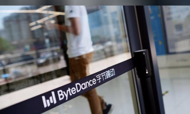 FILE PHOTO: A man walks by a logo of Bytedance, the China-based company which owns the short video app TikTok, or Douyin, at its office in Beijing, China July 7, 2020.
