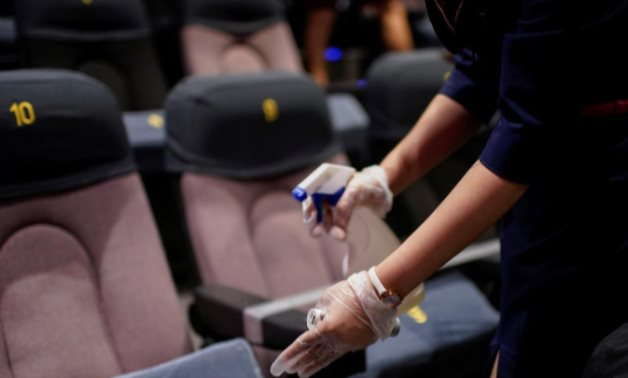 A staff member disinfects seats in a cinema as it reopens following the coronavirus disease (COVID-19) outbreak, in Shanghai, China July 20, 2020. REUTERS/Aly Song