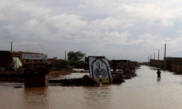 A file photo shows a man walks past the remains of a house destroyed by floods caused by heavy rains in Khartoum, Sudan. (Reuters)