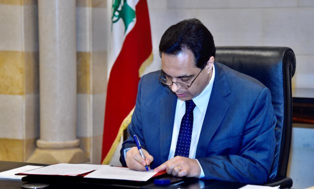 Lebanon's Prime Minister Hassan Diab signs a request for assistance from the International Monetary Fund, May 1, 2020. Dalati Nohra/Handout via Reuters
