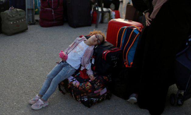 A girl rests as she waits before leaving the Palestinian Rafah border crossing with Egypt, August 12, 2020. REUTERS/Mohammed Salem
