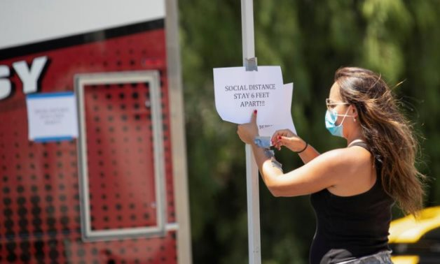 """FILE PHOTO: A person places a sign reminding about social distancing on the set of the film """"7th & Union"""" during the outbreak of (COVID-19), in Pomona, California, U.S., July 8, 2020. REUTERS/Mario Anzuoni"""