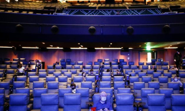 """People take their seats inside the Odeon Luxe Leicester Square cinema, on the opening day of the film """"Tenet"""", amid the  (COVID-19) outbreak, in London, Britain, August 26, 2020. REUTERS/Henry Nicholls"""