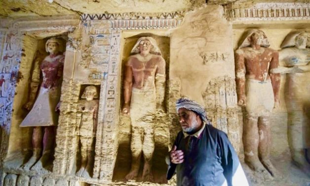 An Egyptian archaelogical laborer is seen walking near deities in a newly discovered tomb at Saqqara necropolis, on Saturday. (AFP)