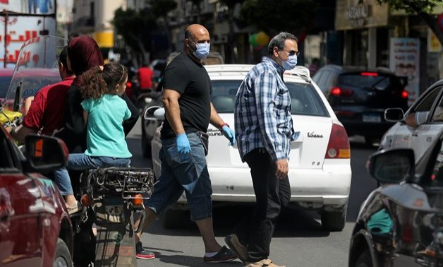 FILE - Men wearing protective face masks walk in downtown Cairo, amidst concerns about the spread of the coronavirus disease (COVID-19), Egypt, May 2, 2020. REUTERS/Mohamed Abd El Ghany