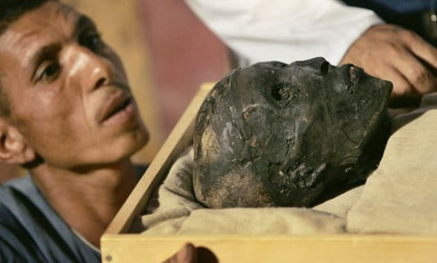 An upper Egyptian looking in amazement to the mummy of King Tutankhamun, who died at the age of 18 or 19 - Press photo