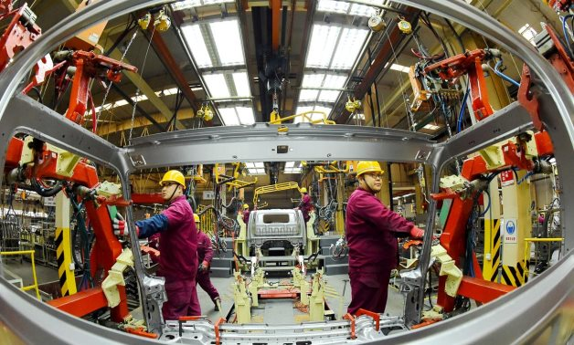 FILE PHOTO: Employees work on a production line manufacturing light trucks at a JAC Motors plant in Weifang, Shandong province, China November 30, 2018. REUTERS/Stringer/File Photo