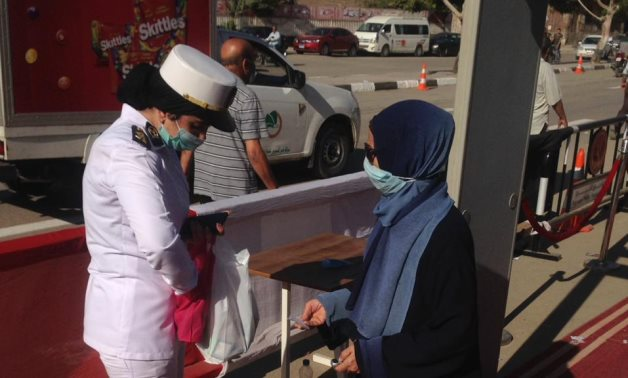 A policewoman and a voter outside a polling station Oct. 24, 2020 - Youm7