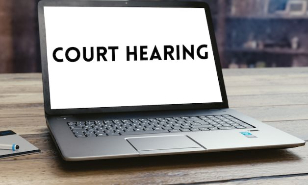 """A laptop with """"Court hearing"""" phrase- photo/ Egypt Today"""