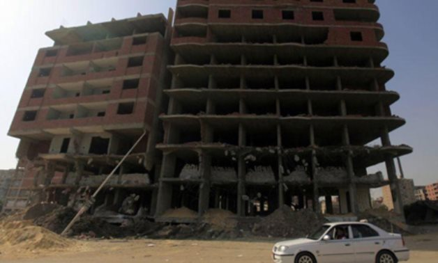 File photo:A taxi moves past blocks of houses that were built illegally and destroyed by the government, behind the Supreme Constitutional Court in Maadi, south of Cairo, REUTERS