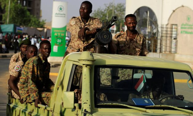 Sudanese soldiers driving an army vehicle in the capital Khartoum - Reuters