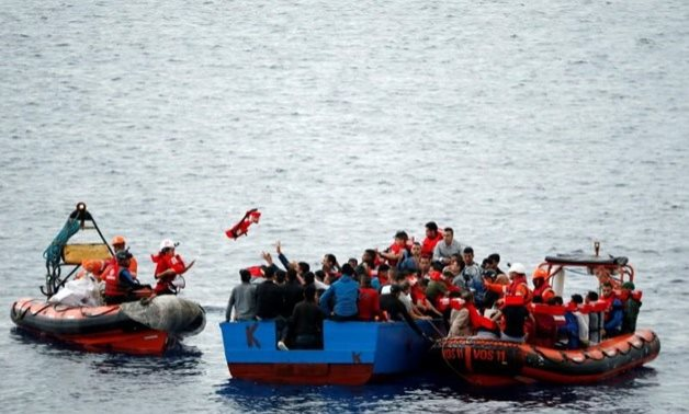 """FILE - Migrants on a wooden boat are rescued by """"Save the Children"""" NGO crew from the ship Vos Hestia in the Mediterranean sea off Libya coast, June 18, 2017."""