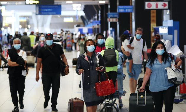 File- Passengers wearing protective masks walk to the check-in counters at the O.R. Tambo International Airport in Johannesburg, South Africa, December 22, 2020. REUTERS/Siphiwe Sibeko