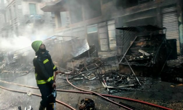A firefighter deals with a huge fire broke out through shops and buildings in Tawfiqia market – Cairo governorate
