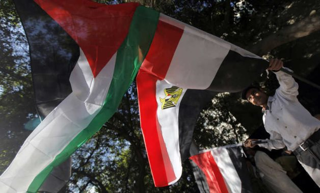 An Egyptian holds Egyptian and Palestinian flags in Cairo, Egypt, Nov. 15, 2012. Photo by REUTERS/Amr Abdallah Dalsh