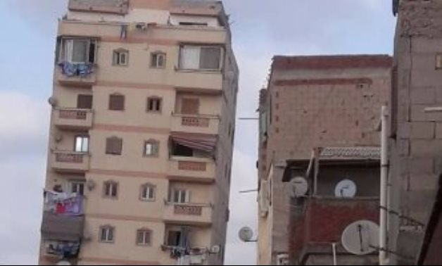 A photo shows a leaning building in Alexandria before it was demolished in February