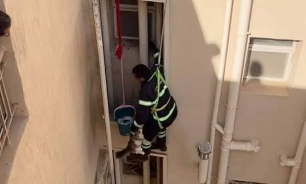 A civil protection unit rescued a cat that had been stuck for a week behind a water pipe in the back of a residential building in New Cairo