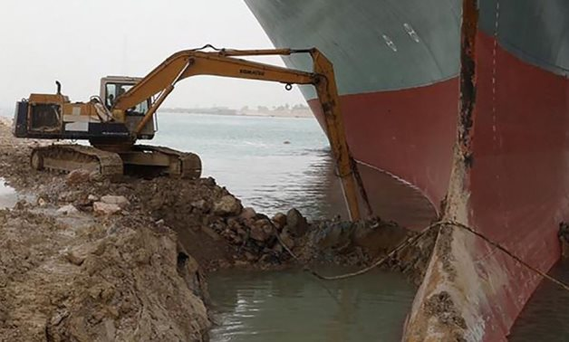 Tiny excavator removes mud and sands around the Ever Given when it went aground in the Suez Canal- press photo