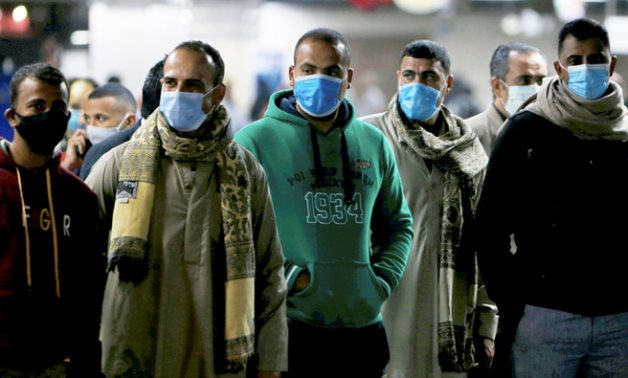 Men in protective masks wait for the train at a metro station in Cairo. (Reuters)